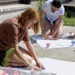 młoda kobieta nakleja wycinek z gazety na duży arkusz białego papieru