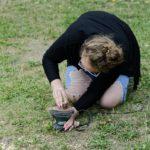 Kobieta klęcząca na trawie wygładza element na szlifierce oscylacyjnej.