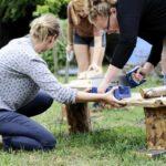 Dwie kobiety przecinają piłą drewniany element leżący na ławeczce.