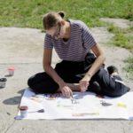 Kobieta siedząca na betonie przy arkuszu papieru nakleja na niego wycięte elementy z kolorowych gazet