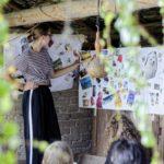 Kobieta stojąca przy arkuszach papieru przywieszonych na ścianie, na których są przyklejone zdjęcia, pocztówki i wycinki z gazet.