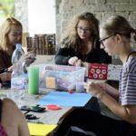 kilka kobiet lepi z plasteliny wspólnie przy stole